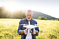 Portrait of senior man with drone on a meadow - HAPF01875