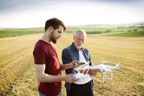 Senior father and his adult son with drone on a field - HAPF01878
