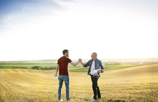 Senior father and his adult son with drone on a field - HAPF01881