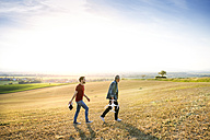 Senior father and his adult son with drone on a field - HAPF01884