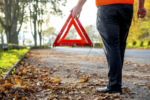 Legs of man with warning triangle at roadside - PUF00656