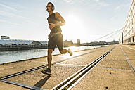 Young athlete jogging in the city at the river - UUF11136