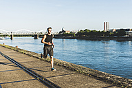 Young athlete jogging in the city at the river - UUF11139