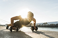 Fit athlete doing push ups at the river - UUF11145