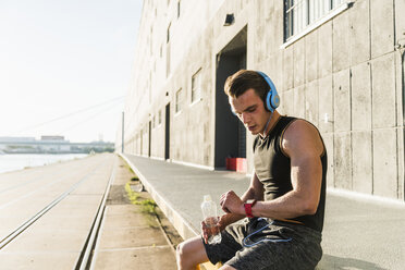 Young athlete wearing headphones, sitting on a wall, checking smartwatch - UUF11148