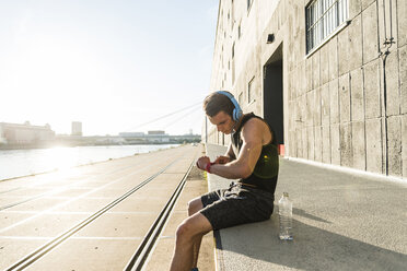 Young athlete wearing headphones, sitting on a wall, checking smartwatch - UUF11151