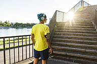 Young athlete jogging up stairs in the city - UUF11154