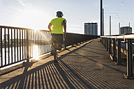 Young athlete jogging on a bridge in the city - UUF11157