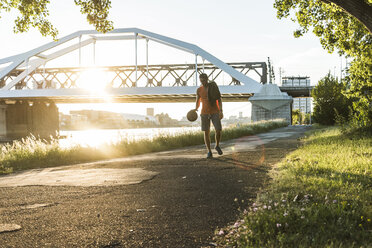 Young man dribbling basketball at the river - UUF11160