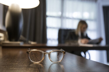 Spectacles on desk with businesswoman checking documents in the background - CHPF00412