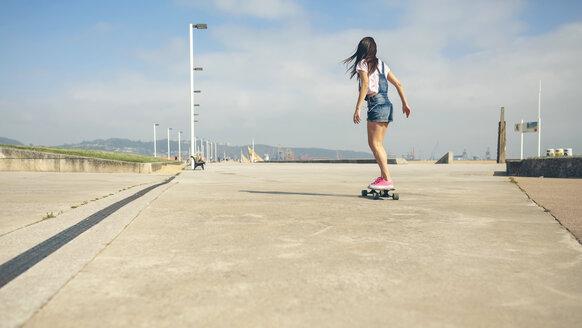 Back view of young woman longboarding on beach promenade - DAPF00771