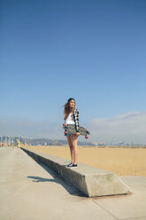 Young woman with longboard standing on a wall at beach promenade - DAPF00780