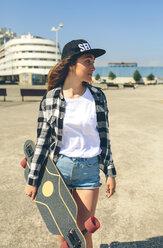 Young woman with longboard on beach promenade - DAPF00783