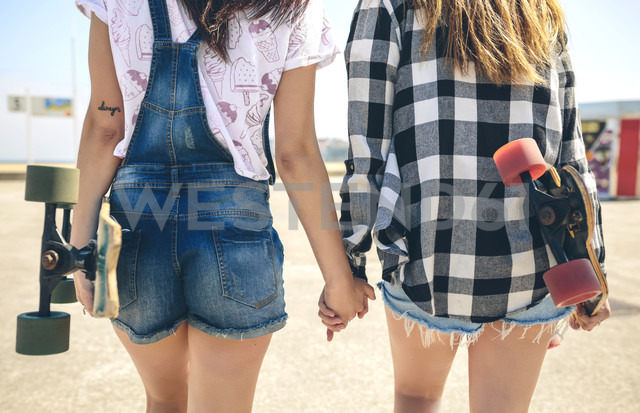 Back view of two young women with longboards walking hand in hand on beach promenade, partial view - DAPF00786