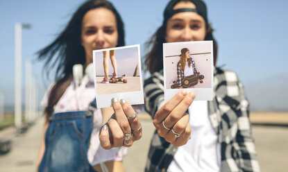 Two young women showing instant photos with their longboards - DAPF00789