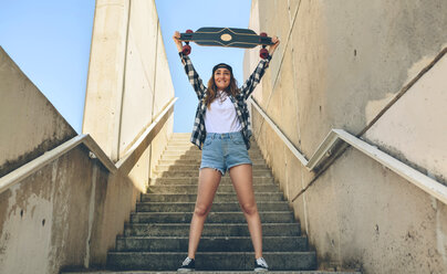 Portrait of happy young woman standing on staircase holding up her longboard - DAPF00795