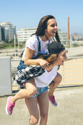 Young woman giving her friend a piggyback ride on roof terrace - DAPF00801