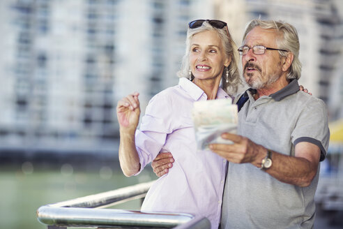 Senior couple taking a city break, holding map - ZEF14145