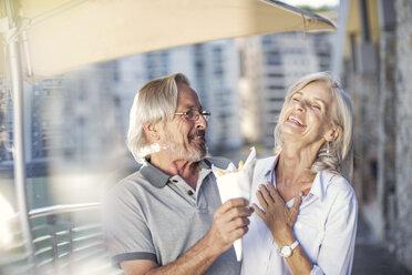 Senior couple taking a city break, eating French fries - ZEF14160