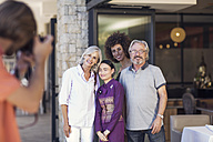 Family taking pictures with Asian waitress in front of restaurant - ZEF14169