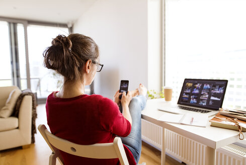 Woman sitting at desk at home using smartphone - HAPF01912