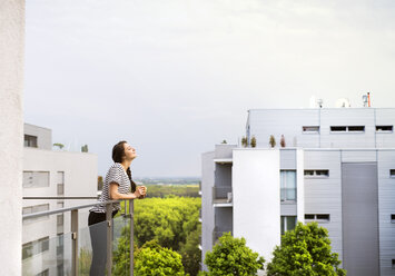 Woman with cup of coffee standing on balcony - HAPF01915