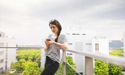 Woman using smartphone on balcony - HAPF01918