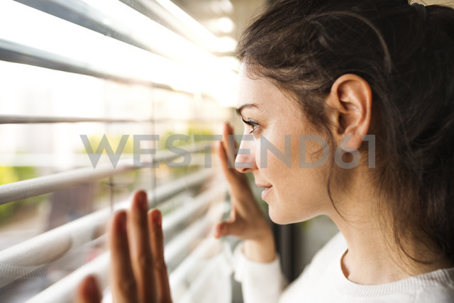 Woman at home looking out of the window - HAPF01942