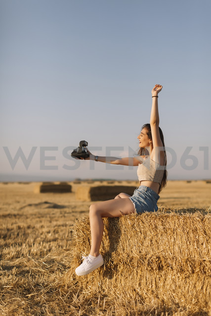 Young woman sitting on straw bale taking selfie with instant camera - JPF00250 - Javier Pardina/Westend61