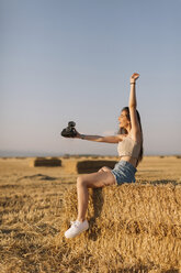 Young woman sitting on straw bale taking selfie with instant camera - JPF00250