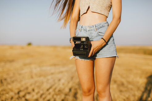 Young woman with instant camera on a field at sunset, partial view - JPF00253