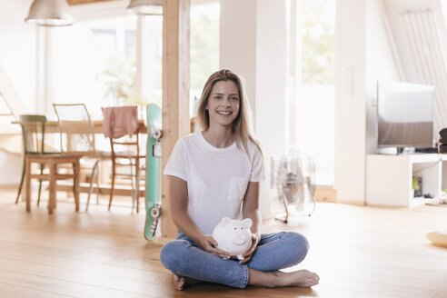 Woman sitting on floor holding piggy bank - GUSF00103