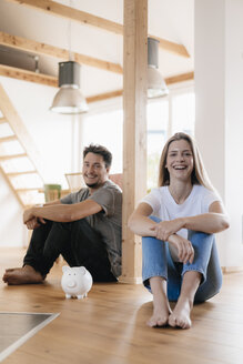 Couple sitting in new home with a piggy bank - GUSF00136