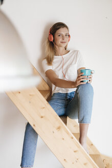 Young woman sitting on wooden stairs, listening music and drinking tea - GUSF00157