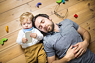 Father lying on floor with his little son playing with smartphone - HAPF01970