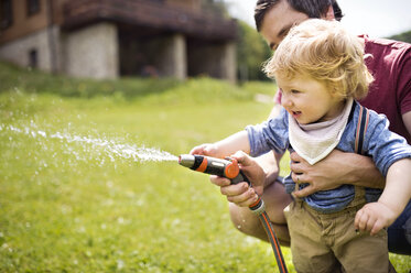 Little boy with his father watering the lawn - HAPF02000