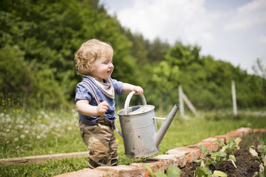 Little boy in the garden watering seedlings - HAPF02012