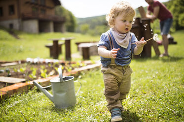 Boy in garden with watering can and father in background - HAPF02015