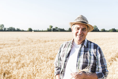 Portrait of laughing senior farmer standing in front of a field - UUF11175