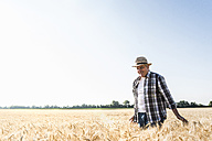 Happy senior farmer walking in wheat field - UUF11178