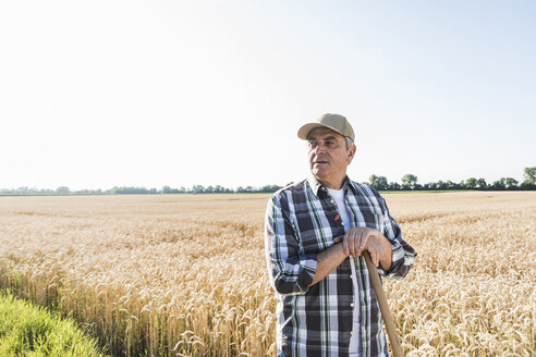 Senior farmer standing in front of wheat field watching something - UUF11181