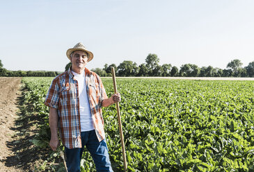 Portrait od smiling senior farmer  standing in front of a field - UUF11199