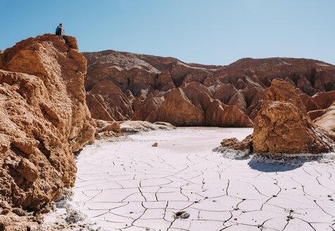 Chile, Atacama Desert, man sitting on a red rock  looking at view - GEMF01741