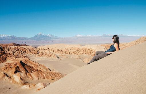 Chile, Atacama Desert, woman sitting on dune looking at view - GEMF01744