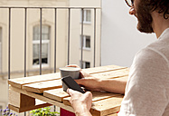 Man sitting with coffee mug on balcony using cell phone - MFRF00878