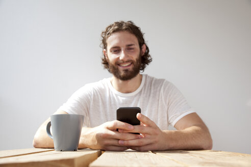 Portrait of smiling man sitting with coffee mug on balcony using cell phone - MFRF00881
