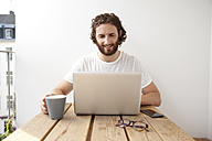 Portrait of smiling man sitting with coffee mug on balcony using laptop - MFRF00884