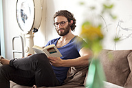 Portrait of smiling young man reading  book in a coffee shop - MFRF00896
