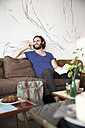 Portrait of young man on the phone sitting on couch in a coffee shop with book - MFRF00899