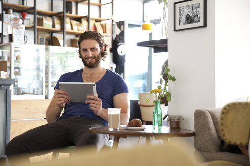 Portrait of young man sitting in a coffee shop using tablet - MFRF00911